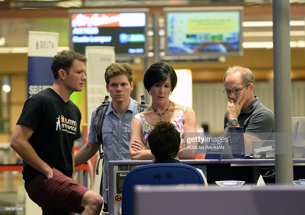 Rick Todd (R) and his wife Mary (2nd R) with their two sons, John (L) and Dylan (2nd L) wait at the departure hall check-in counter of Changi International Airport in Singapore on May 23, 2013. Two US pathologists on May 22 supported Singapore police findings that American scientist Shane Todd found hanged last year in the city-state committed suicide and was not murdered as his family claims. .