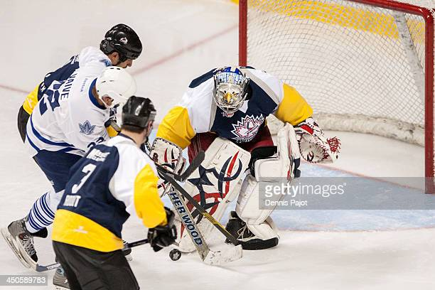 Rick Vaive of the Toronto Maple Leafs Alumni battles against Bob Boughner and Jimi St John of the Windsor Spitfires Alumni on November 8 2013 at the...