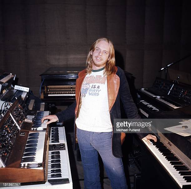 Rick Wakeman portrait circa 1977 wearing a tshirt which reads 'Pollution Is A Dirty Word' The keyboards around him include a Mellotron and Minimoog...