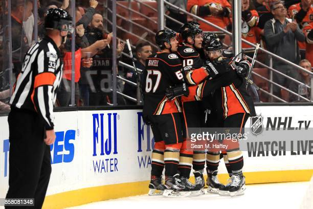 Rickard Rakell and Andrew Cogliano congratulate Corey Perry of the Anaheim Ducks after his goal during the first period of a game against the Arizona...