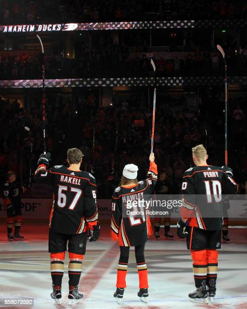 Rickard Rakell and Corey Perry of the Anaheim Ducks join this year's '21st Duck' Katie Hawley as she signals to the crowd prior to the game against...
