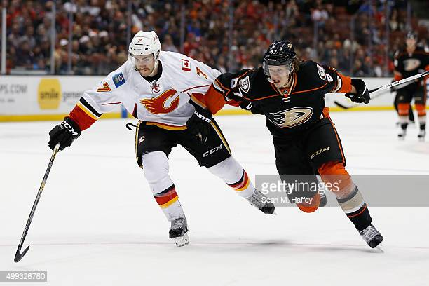 Rickard Rakell of the Anaheim Ducks and TJ Brodie of the Calgary Flames battle for a loose puck during the third period of a game at Honda Center on...