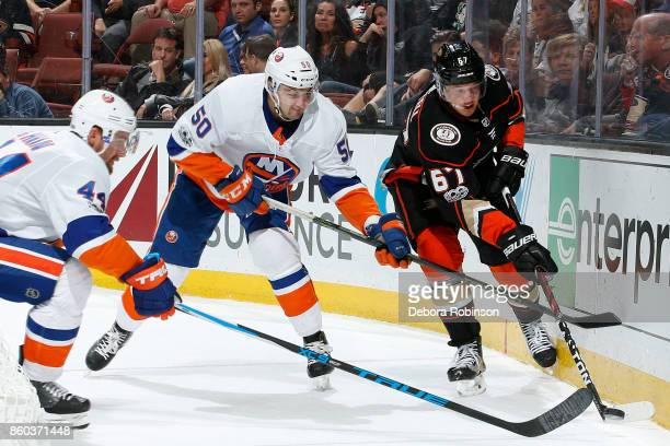 Rickard Rakell of the Anaheim Ducks battles for the puck against Adam Pelech and Calvin de Haan of the New York Islanders during the game on October...