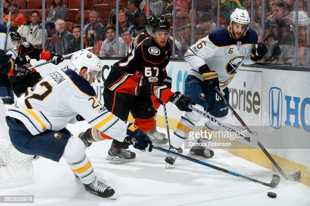 Rickard Rakell of the Anaheim Ducks battles for the puck against Marco Scandella and Johan Larsson of the Buffalo Sabres during the game on October...