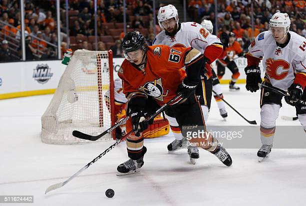 Rickard Rakell of the Anaheim Ducks chases a loose puck as Deryk Engelland and Matt Stajan of the Calgary Flames defend during the first period of a...