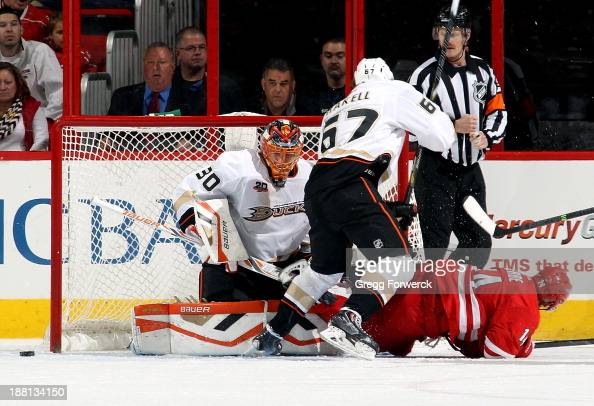 Rickard Rakell of the Anaheim Ducks defends Nathan Gerbe of the Carolina Hurricanes as the puck goes wide of Viktor Fasth of the Ducks during their...