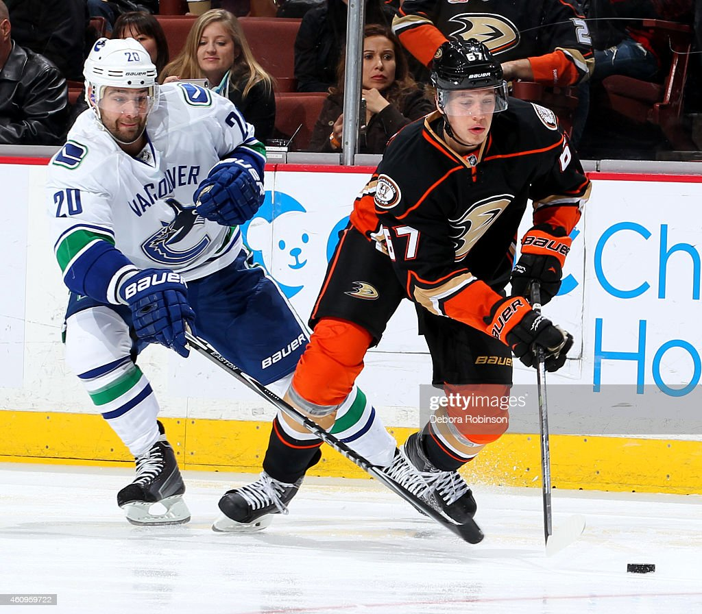 Rickard Rakell #67 of the Anaheim Ducks handles the puck against Chris Higgins #20 of the Vancouver Canucks on December 28, 2014 at Honda Center in Anaheim, California.