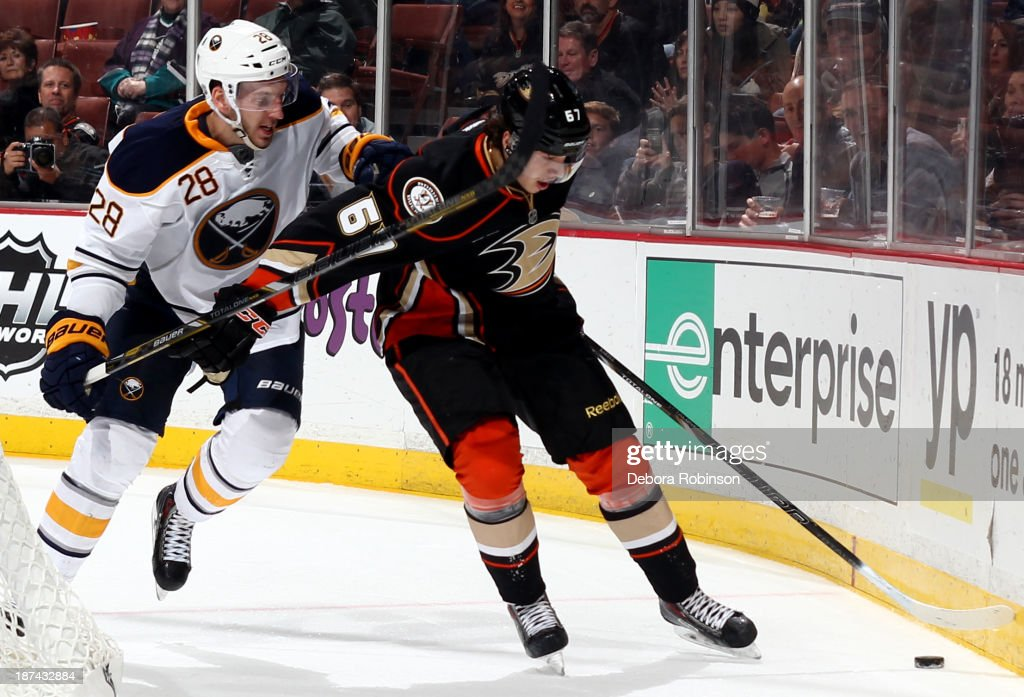 Rickard Rakell #67 of the Anaheim Ducks handles the puck while being guarded by <a gi-track='captionPersonalityLinkClicked' href=/galleries/search?phrase=Zemgus+Girgensons&family=editorial&specificpeople=8050732 ng-click='$event.stopPropagation()'>Zemgus Girgensons</a> #28 of the Buffalo Sabres at Honda Center on November 8, 2013 in Anaheim, California.