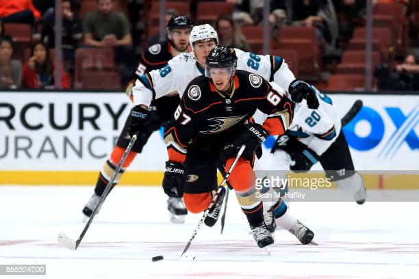 Rickard Rakell of the Anaheim Ducks skates with the puck past Timo Meier of the San Jose Sharks during the first period of a preseason game at Honda...