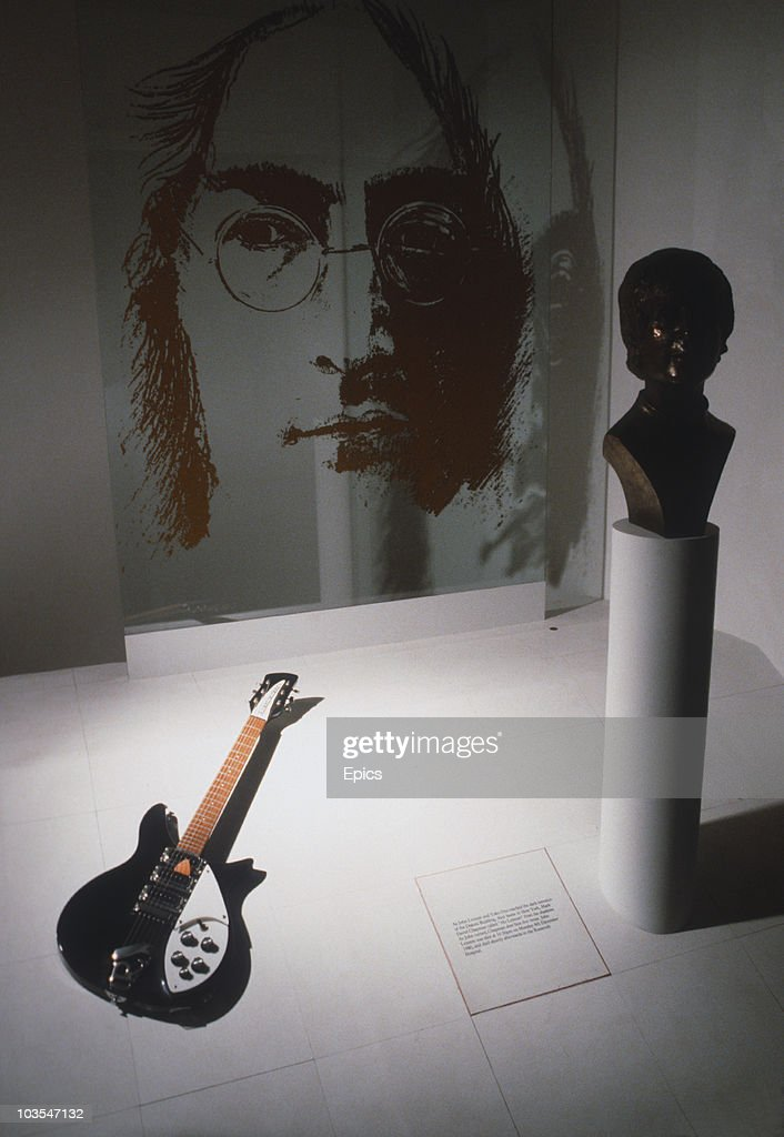 A Rickenbacker guitar belonging to former Beatle John Lennon on display along with a bust and artwork of the singer in his hometown of Liverpool, May 1987.