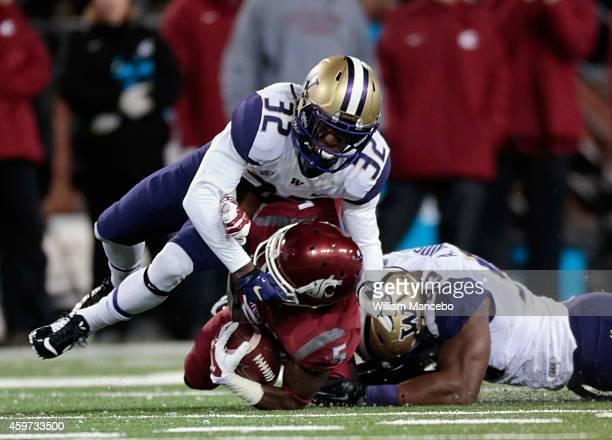 Rickey Galvin of the Washington State Cougars is tackled by Budda Baker and Andrew Hudson of the Washington Huskies in the first half of the 107th...