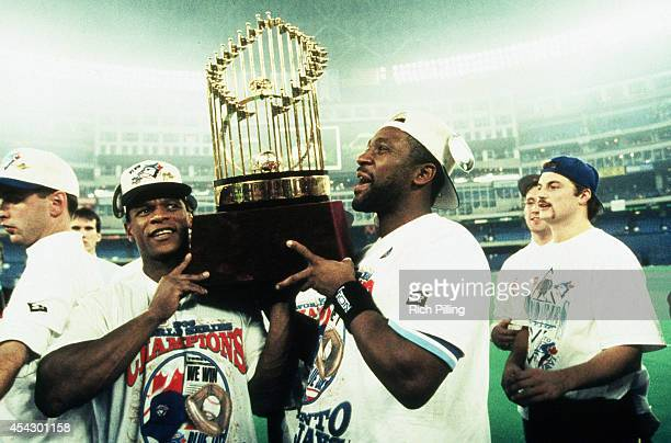 Rickey Henderson and Joe Carter of the Toronto Blue Jays carry the World Series trophy after the Blue Jays victory during World Series game six...