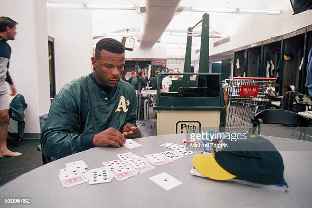 Rickey Henderson of the Oakland Athletics plays solitaire before the game against the Boston Red Sox at OaklandAlameda Coliseum on April 1 1998 in...