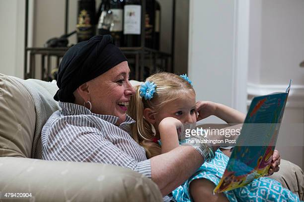 Ricki Harvey reads a children's book to her granddaughter Lilly Harvey at her home in McLean Va on June 30 2015