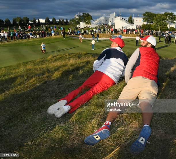 Rickie Fowler and caddy Michael Greller watch play on the 17th hole during the afternoon fourball matches at the Presidents Cup at Liberty National...