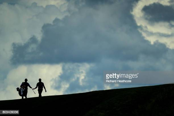 Rickie Fowler and his caddy Joe Skovron walk down the 12th hole during the third round of the 2017 US Open at Erin Hills on June 17 2017 in Hartford...