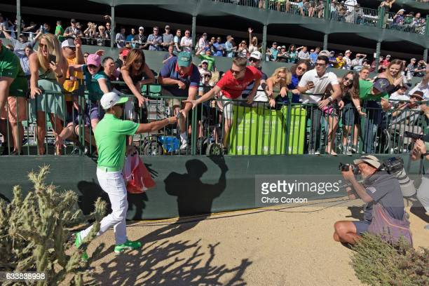 Rickie Fowler hands out gifts to fans at the 16th hole during the third round of the Waste Management Phoenix Open at TPC Scottsdale on February 4...