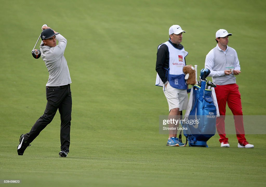 <a gi-track='captionPersonalityLinkClicked' href=/galleries/search?phrase=Rickie+Fowler&family=editorial&specificpeople=4466576 ng-click='$event.stopPropagation()'>Rickie Fowler</a> hits a shot on the 15th hole as <a gi-track='captionPersonalityLinkClicked' href=/galleries/search?phrase=Rory+McIlroy&family=editorial&specificpeople=783109 ng-click='$event.stopPropagation()'>Rory McIlroy</a> watches on during the first round of the 2016 Wells Fargo Championship at Quail Hollow Club on May 5, 2016 in Charlotte, North Carolina.