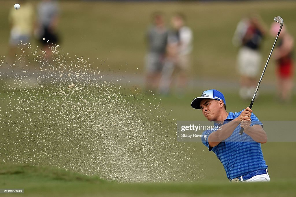 Rickie Fowler hits his third shot from a green side bunker on the 18th hole during a continuation of the second round of the Zurich Classic at TPC Louisiana on April 30, 2016 in Avondale, Louisiana.