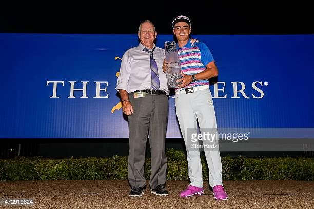 Rickie Fowler holds the championship trophy with his swing coach Butch Harmon after winning in a sudden death playoff during the final round of THE...