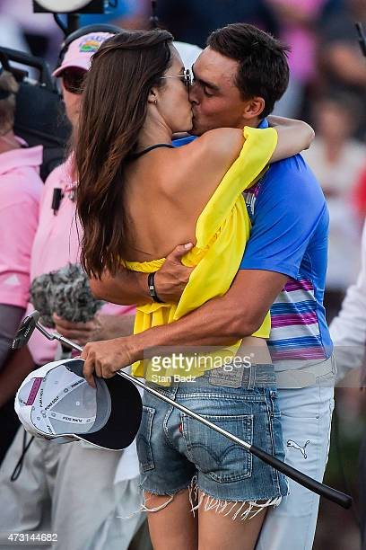 Rickie Fowler kisses his girlfriend Alexis Randock after winning in a sudden death playoff on the 17th hole green during the final round of THE...