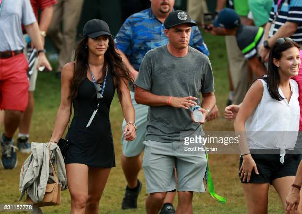 Rickie Fowler of the United States and Allison Stokke walk along the on the 18th green during the final round of the 2017 PGA Championship at Quail...