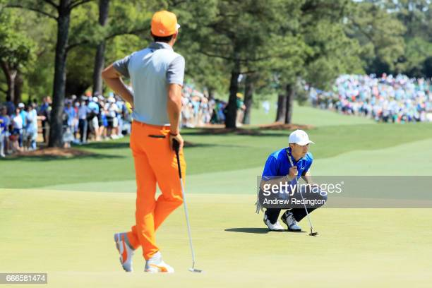 Rickie Fowler of the United States and Jordan Spieth of the United States play the first green during the final round of the 2017 Masters Tournament...