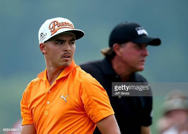 Rickie Fowler of the United States and Phil Mickelson of the United States look on from the first hole tee during the final round of the 96th PGA...