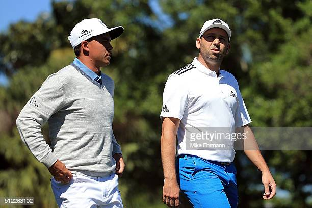 Rickie Fowler of the United States and Sergio Garcia of Spain walk down the third fairway during the first round of the Honda Classic at PGA National...