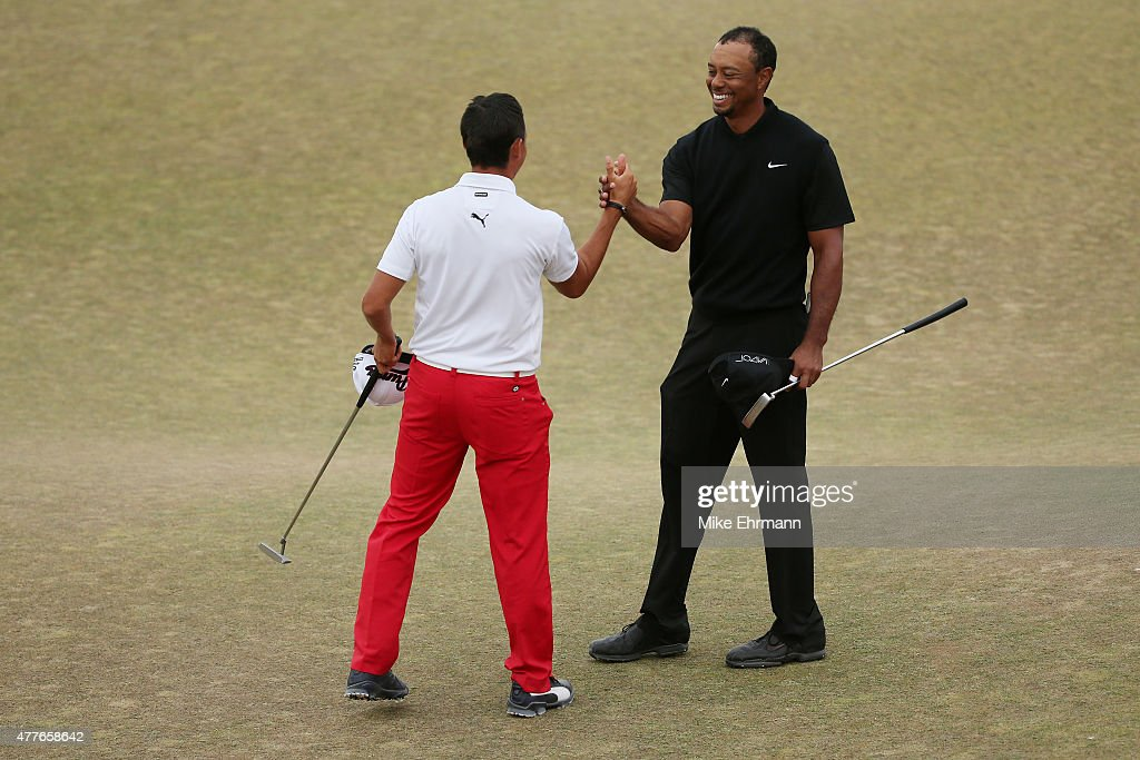 Rickie Fowler of the United States and Tiger Woods of the United States shake hands on the 18th green after completing their first round of the 115th U.S. Open Championship at Chambers Bay on June 18, 2015 in University Place, Washington.