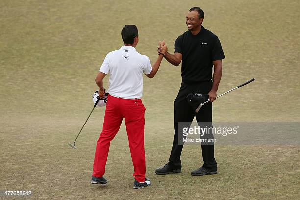 Rickie Fowler of the United States and Tiger Woods of the United States shake hands on the 18th green after completing their first round of the 115th...