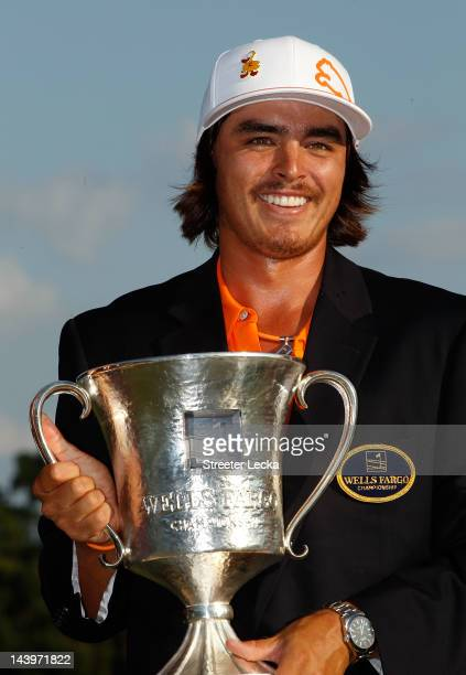 Rickie Fowler of the United States celebrates with the championship trophy after defeating Rory McIlroy of Northern Ireland and DA Points of the...