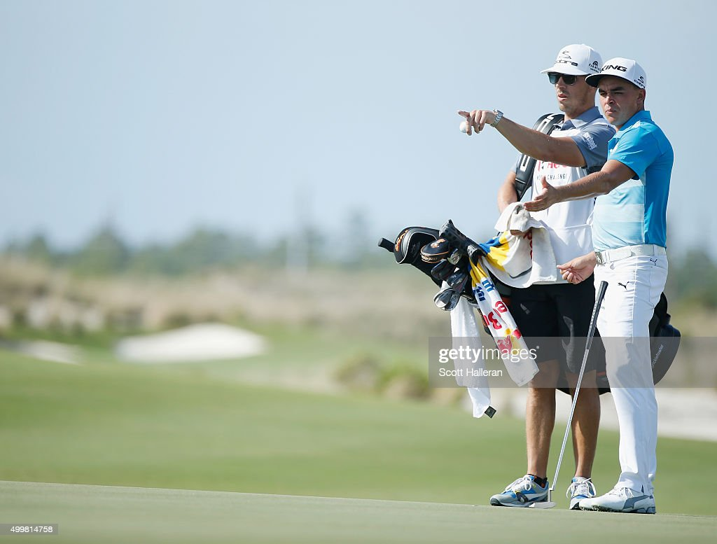 Rickie Fowler of the United States chats with his caddie Joe Skovron on the 12th green during the first round of the Hero World Challenge at Albany, The Bahamas on December 3, 2015 in Nassau, Bahamas