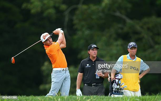 Rickie Fowler of the United States hits a tee shot on the fourth hole as Phil Mickelson of the United States and caddie Jim 'Bones' Mackay look on...