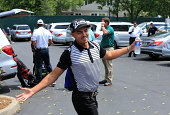 Rickie Fowler of the United States jokingly poses for photographers as Tiger Woods of the United States arrives to the course for a practice round...