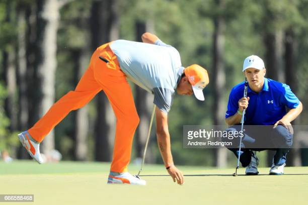 Rickie Fowler of the United States marks his ball as Jordan Spieth of the United States looks on from the eighth hole during the final round of the...