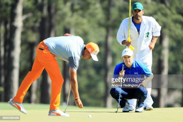 Rickie Fowler of the United States marks his ball as Jordan Spieth of the United States and caddie Michael Greller look on from the eighth hole...