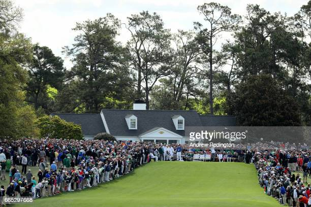Rickie Fowler of the United States plays a shot on the first tee as a gallery of patrons looks on during the first round of the 2017 Masters...