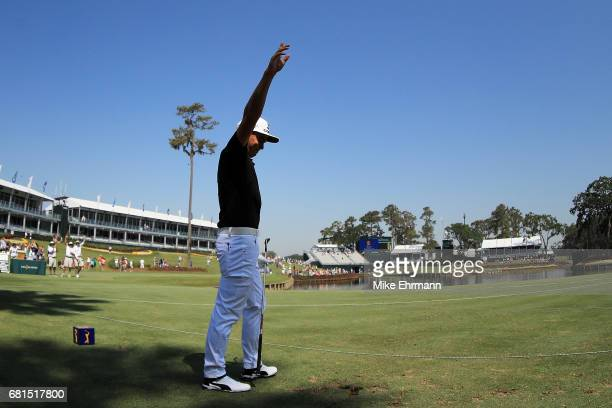 Rickie Fowler of the United States reacts after making a hole in one on the 17th hole during a practice round prior to THE PLAYERS Championship at...