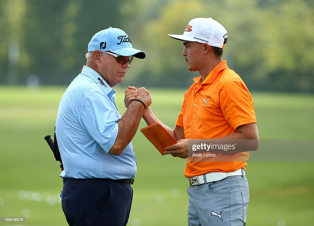 Rickie Fowler of the United States shakes hands with his instructor Butch Harmon on the practice range during the final round of the 96th PGA...