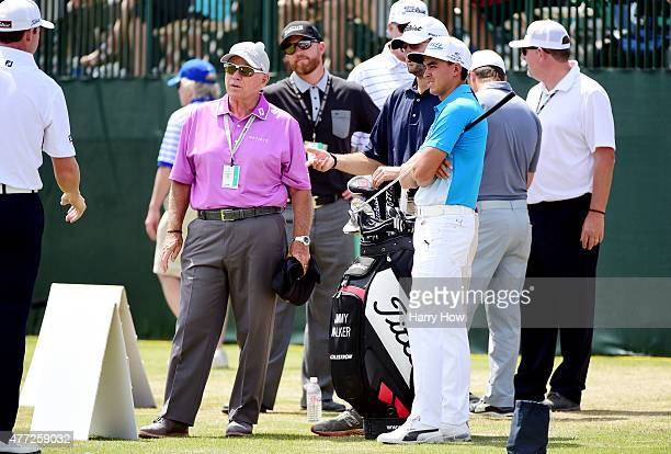 Rickie Fowler of the United States speaks with his coach Butch Harmon at the driving range before a practice round prior to the start of the 115th US...