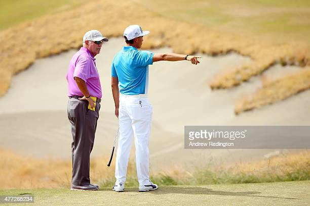 Rickie Fowler of the United States speaks with his coach Butch Harmon during a practice round prior to the start of the 115th US Open Championship at...
