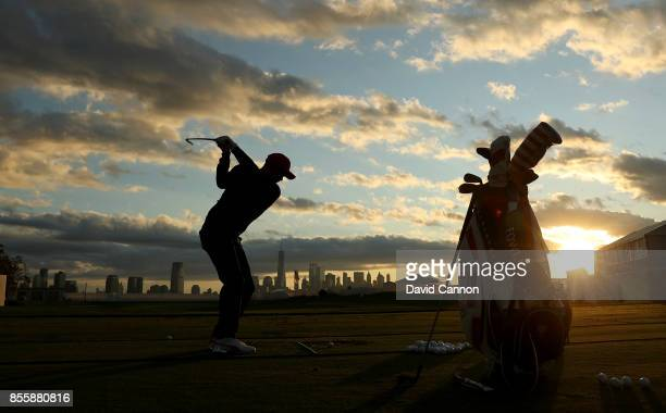 Rickie Fowler of the United States team warms up on the driving range as the sun rises over Manhattan during the Saturday morning foursomes matches...
