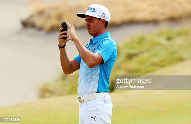 Rickie Fowler of the United States uses his mobile phone during a practice round prior to the start of the 115th US Open Championship at Chambers Bay...