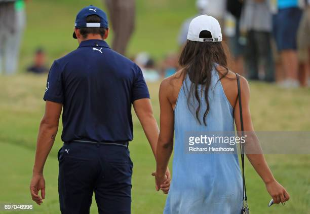 Rickie Fowler of the United States walks off the course with Allison Stokke after finishing during the third round of the 2017 US Open at Erin Hills...