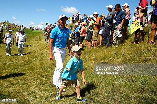 Rickie Fowler of the United States walks with a young golfer during a practice round prior to the 2015 PGA Championship at Whistling Straits on...