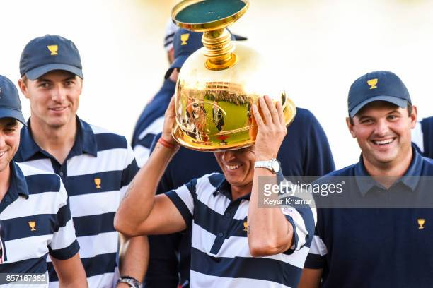 Rickie Fowler of the US Team with teammates Jordan Spieth and Patrick Reed jokingly puts the Presidents Cup trophy on his head while celebrating his...