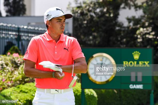 Rickie Fowler puts on his glove on the first hole tee box in front of the Rolex clock during the first round of the World Golf ChampionshipsMexico...