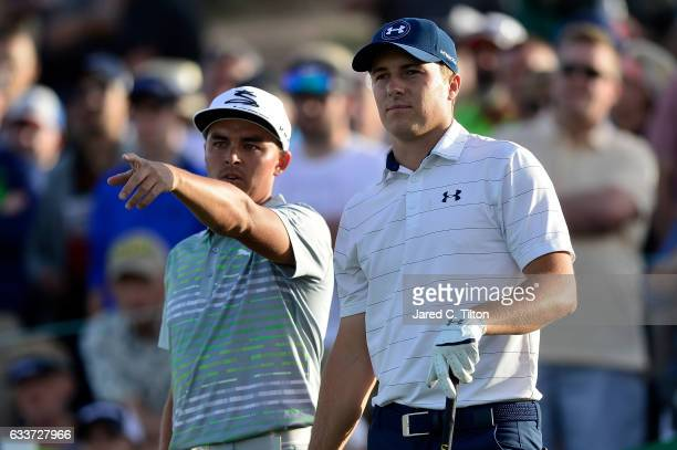 Rickie Fowler shows Jordan Spieth where his tee shot went into the water hazard on the 18th hole during the second round of the Waste Management...
