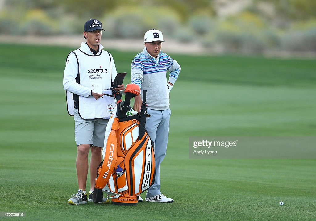 Rickie Fowler stands with his caddie before playing a shot during the first round of the World Golf Championships - Accenture Match Play Championship at The Golf Club at Dove Mountain on February 19, 2014 in Marana, Arizona.